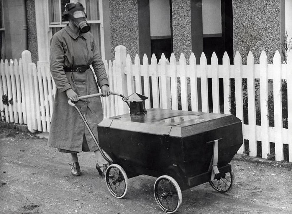 A woman with a baby carriage equipped against gas attacks england 1938