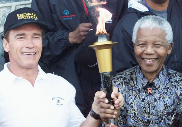 Former-President-Nelson-Mandela-and-Arnold-Schwarzenegger-hold-a-symbolic-Flame-of-Hope