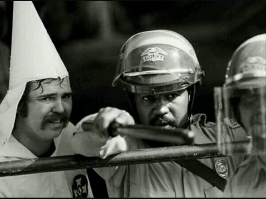 Black officer protecting KKK member from protesters, 1983