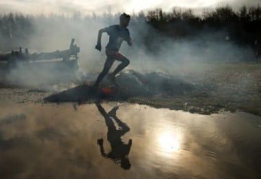 A competitors run through smoke and flames during the Tough Guy event in Perton, central England