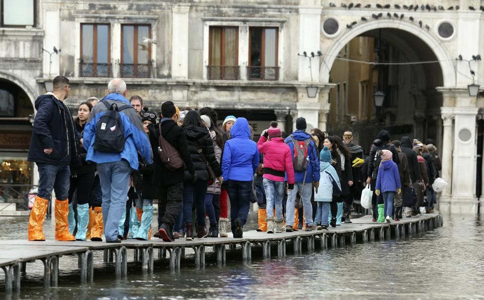 Tourists walk on raised platforms above flood waters during a period of seasonal high water and on the first day of carnival, in Venice
