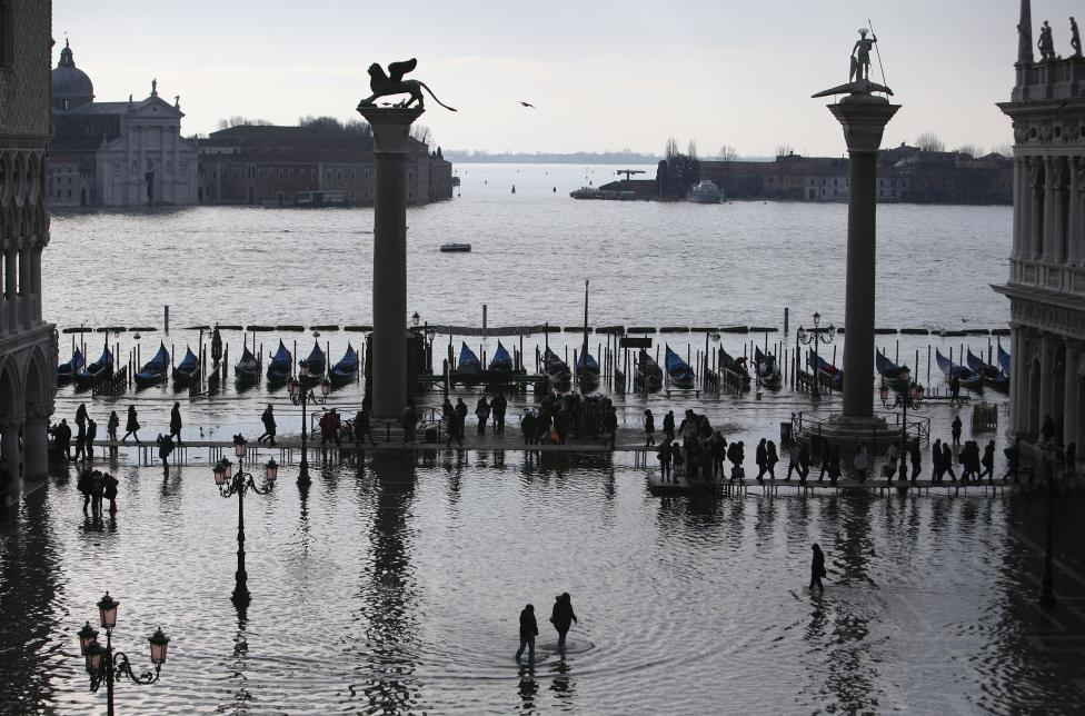 People walk through flood water at St. Mark's Square during a period of seasonal high water in Venice