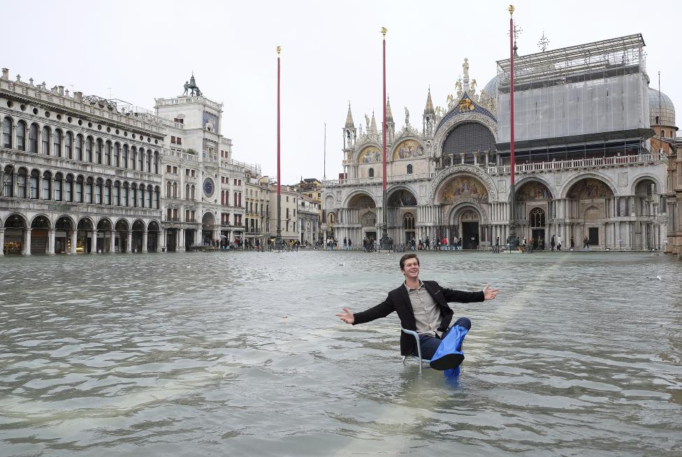 A man poses in a flooded St. Mark's Square during a period of seasonal high water in Venice