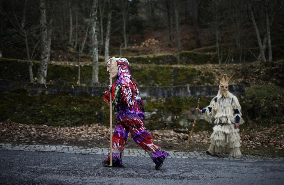 Carnival revellers wearing wooden masks walk as they parade during carnival festivities, in Portugal's northwestern village of Lazarim