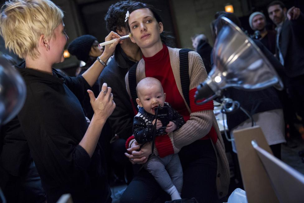 A model holds a baby while being made-up backstage before the Vera Wang Fall/Winter 2015 collection show at New York Fashion Week