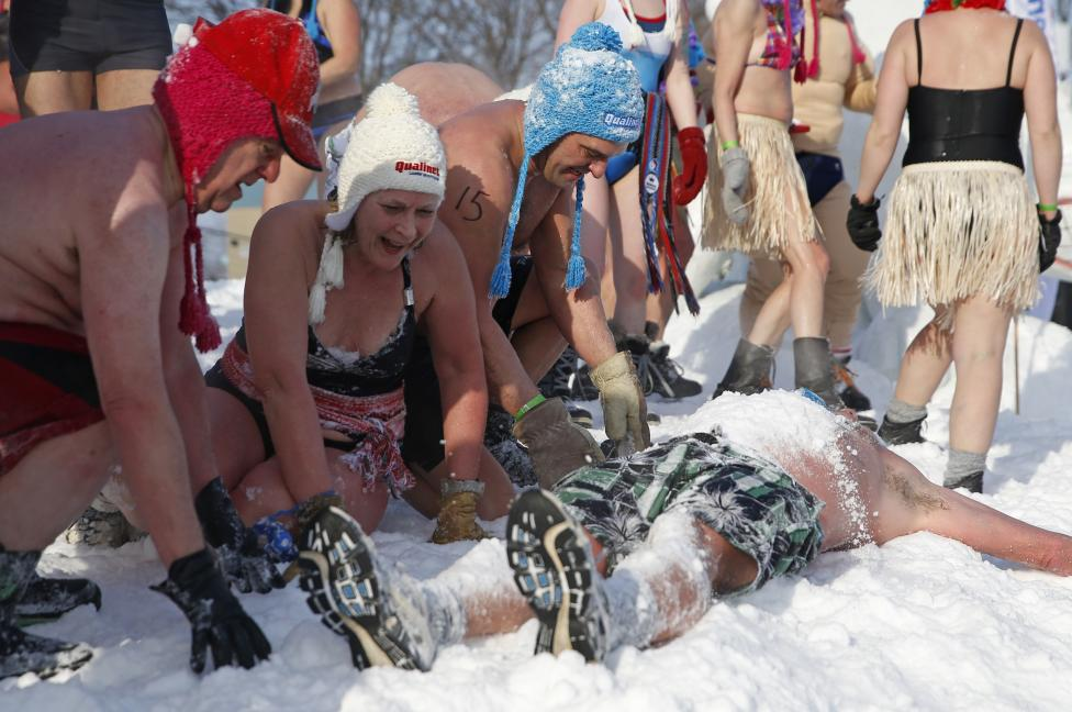 People cover a man with snow during a snow bath at the Quebec Winter Carnival in Quebec City