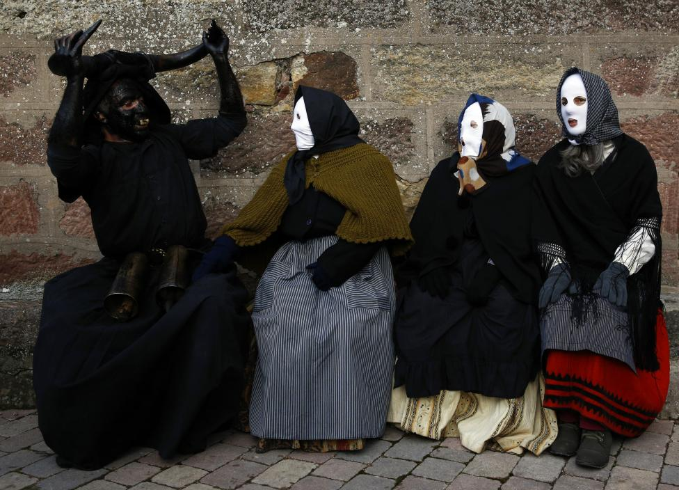 "A reveller dressed as a ""Diablo de Luzon"" (Luzon Devil) sits next to others dressed as Mascaritas"" during carnival celebrations in Luzon"