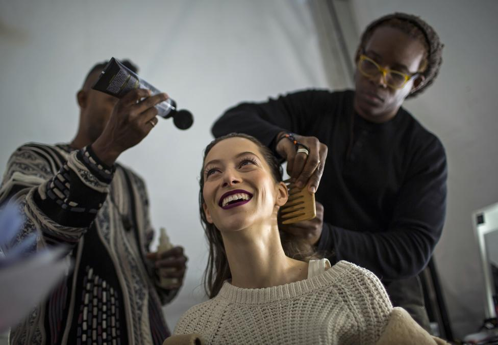 A model is made up backstage before the Carolina Herrera Fall/Winter 2015 collection show during New York Fashion Week