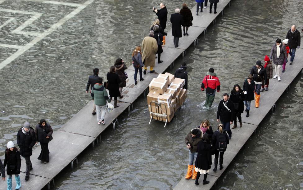 Tourists walk on raised platforms above flood waters in St. Mark's square during a period of seasonal high water in Venice