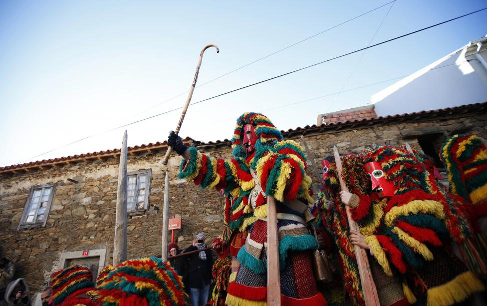 Revellers wearing masks perform during a parade at the carnival festivities, in Portugal's northeastern village of Podence