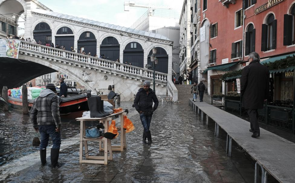 A man sells Wellington boots in flood waters near Rialto Bridge during a period of seasonal high water in Venice