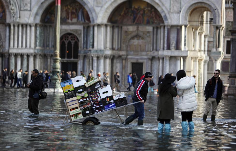 A man pulls a cart carrying fruits and vegetables through a flooded St. Mark's Square during a period of seasonal high water in Venice