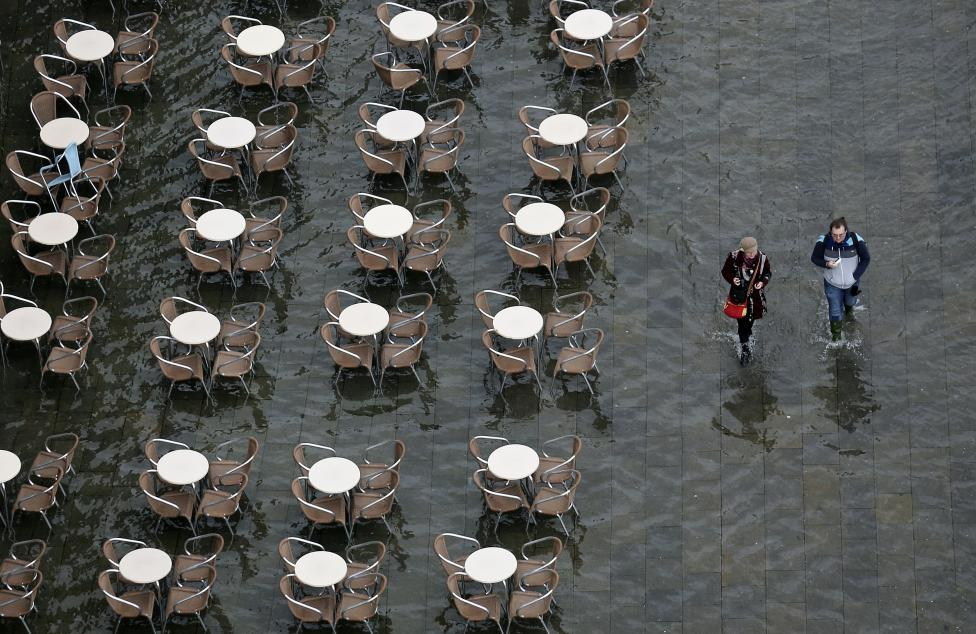 People walk on the flooded St. Mark's Square during a period of seasonal high water and on the first day of carnival, in Venice