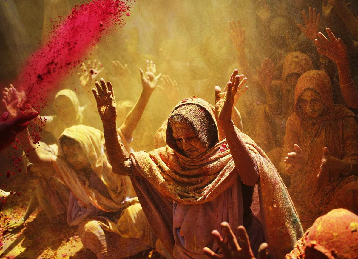 Widows daubed in colors chanted religious hymns as they took part in the Holi celebrations on March 4. (Anindito Mukherjee/Reuters)