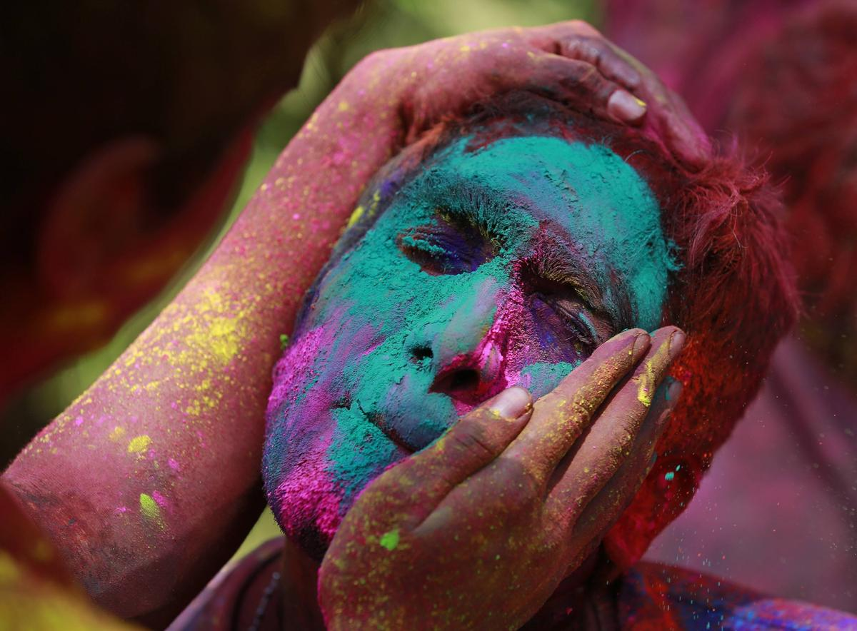 Colored powder was applied to a man's face while celebrating Holi in Mumbai on March 6. (Danish Siddiqui/Reuters)