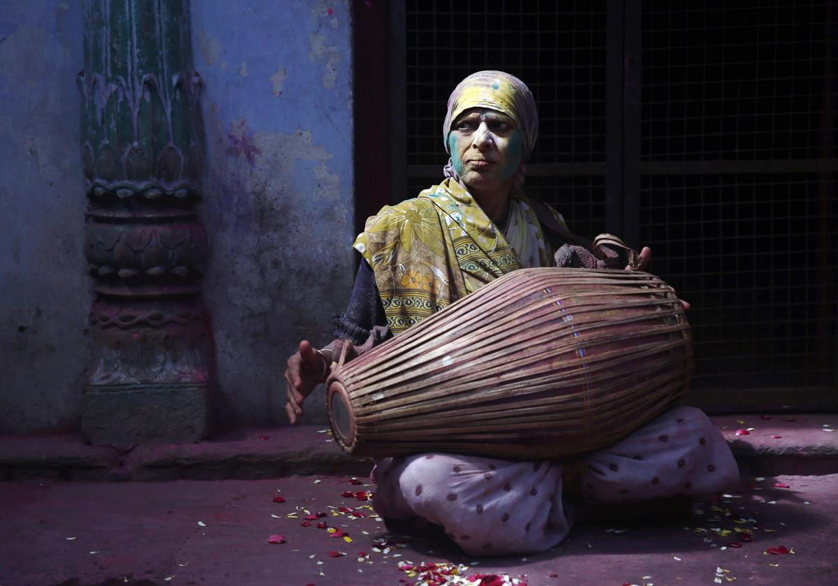 A widow daubed in colors played a drum at a widows' ashram at Vrindavan on March 6. (Ahmad Masood/Reuters)
