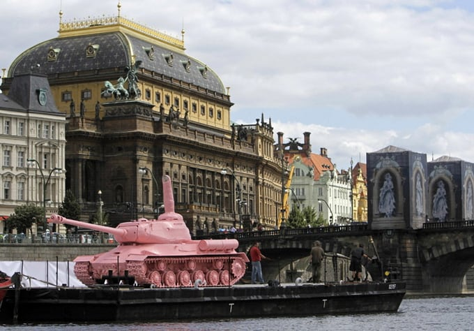 A Soviet WW II tank painted pink is located on a boat in front of the National Theatre in Prague