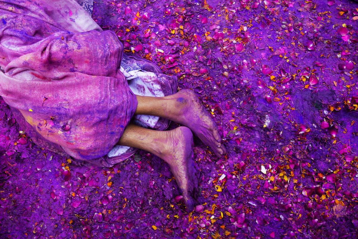 A Hindu widow lay on a sludgy ground filled with a mixture of colored powder, water, and flower petals during celebrations to mark Holi at the Meera Sahabhagini Widow Ashram in Vrindavan, India. (Bernat Armangue/Associated Press)