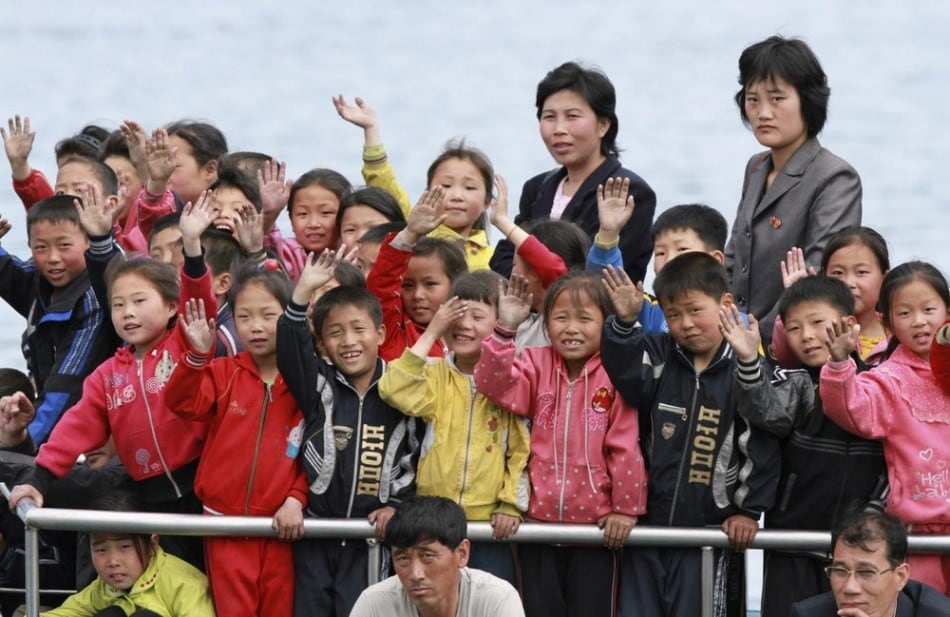 North Korean children wave during their trip on the Yalu River in Sinuiju, opposite the Chinese border city of Dandong, May 15, 2013. (Photo by Jacky Chen/Reuters)
