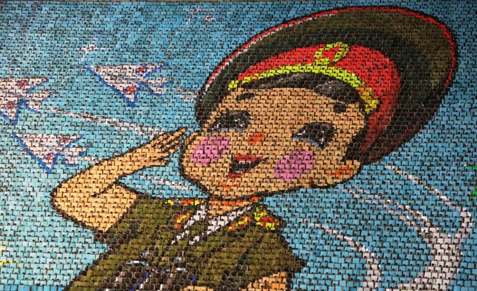 """North Korean students use different colored cardboard to form a picture of a child in uniform as a background during a mass gymnastic and artistic performance """"Arirang"""", in Pyongyang July 26, 2013. The games are the world's biggest choreographed extravaganza, part circus act, part rhythmic gymnastics floor, with plenty of reverence for the late North Korean leader Kim Jong-il. (Photo by Jason Lee/Reuters)"""