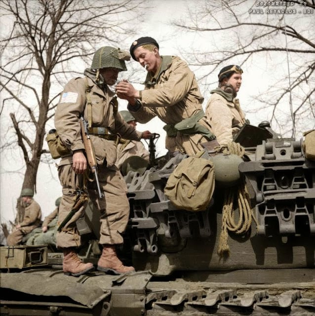 A paratrooper from the American 17th Airborne Division gets a light from a Churchill tank crewman of 6th Guards Armoured Brigade near Dorsten in North Rhine-Westphalia, Germany, 29th of March 1945. (Source - No 5 Army Film & Photographic Unit - © IWM BU 2738. Photographer - Sgt.Midgley. Colorized by Paul Reynolds. Historic Military Photo Colourisations)