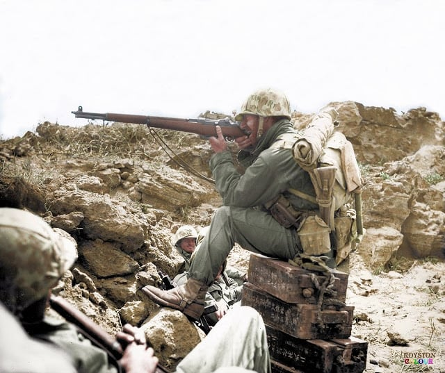 An American Marine aiming his Garand M1 rifle, whilst perched on Japanese ammunition crates on the Island of Iwo Jima, c. February/March 1945. (Colourised by Royston Leonard from the UK)