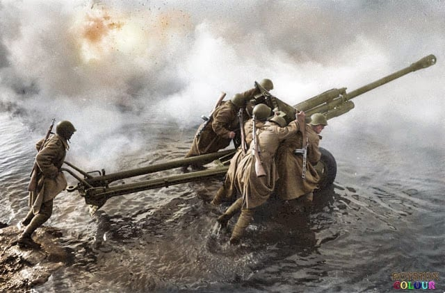 Soviet artillerymen transporting a 76-mm divisional gun M1942 (ZiS-3) during the forced crossing of the Oder River, Germany, c. December, 1944. (Photograph by Dmitri Baltermants. Colorized by Royston Leonard from the UK)