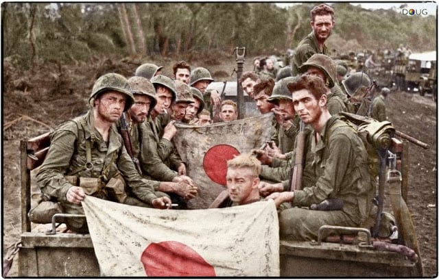 The strain and fatigue of 23 days on the line is shown by Marines of Combat Team 'C', 2/7th US Marines, 1st Marine Division seen here displaying Japanese battle flags captured during the Battle of Cape Gloucester. 14-15th January 1944. (Source USMC 71602. Colorized by Doug)