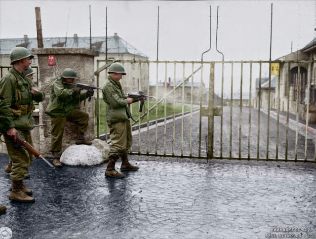 """US troops from Combat Command B of the U.S. 14th Armored Division entering the Hammelburg Prison in Germany by opening the main gate with bursts of their M3 """"Grease Guns"""". Hammelburg, Germany. April 6, 1945. (Colorized by Paul Reynolds. Historic Military Photo Colourisations)"""