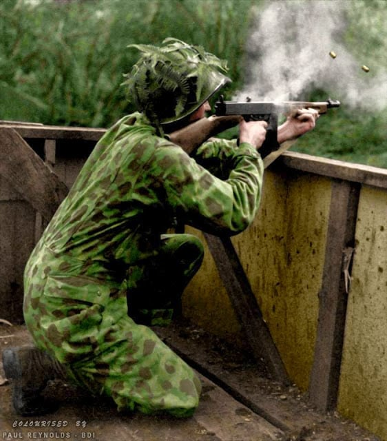 A US Marine wearing his camouflage suit fires a Thompson sub-machine gun during Jungle Training - 1942. (Colorized by Paul Reynolds. Historic Military Photo Colourisations)