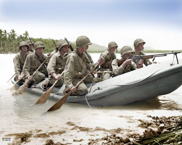 A Browning Automatic Rifle (BAR) man in the bow of the rubber landing craft provides covering fire as a 10-man boat crew of the US Marine 3rd Raider Battalion reaches the undefended beach of Pavuvu in the Russell Islands during 'Operation Cleanslate'. February 1943. (Source - USMC ID #: 54765. Colorized by Royston Leonard UK)