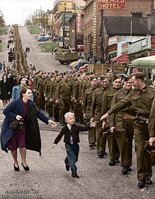 """On October 1, 1940, Private Jack Bernard and other volunteers in The British Columbia Regiment (Duke of Connaught's Own Rifles) were marching smartly down Eighth Street in New Westminster to board a ship and sail off to war. Suddenly, Bernard's five-year-old son broke free of his mother's grasp and sprinted into the military formation to take his smiling father's hand. In that instant, an alert Vancouver Daily Province photographer, Claude Dettloff, snapped the shutter. Soon, his unforgettable image of little Warren """"Whitey"""" Bernard was being printed by leading publications throughout North America. It was later used in Canada's war bond drives with the plea, """"help bring my Daddy home."""" Jack Bernard survived the war and was reunited with his son in 1945. (Claude Dettloff, photographer - City of Vancouver Archives online database. Colorized by Paul Reynolds. Historic Military Photo Colourisations)"""