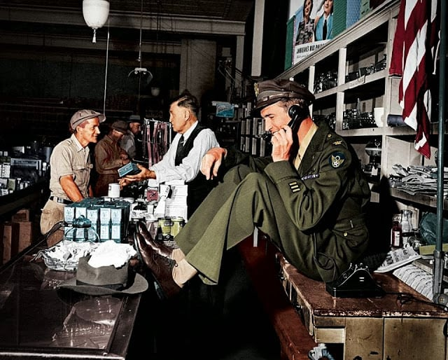 While his father chats with a customer at the hardware store, a uniformed Jimmy Stewart sets up a date to go fishing,1945. (Colorized by John Gulizia from America)