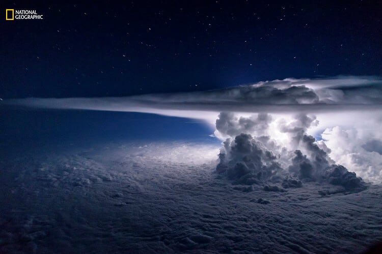 Santiago Borja/2016 National Geographic Nature Photographer of the Year. Pacific Storm. 3rd Place—Landscape: An isolated cumulonimbus storm developed over the Pacific Ocean a few miles south of the coast of Panama City. It sat atop a temperature inversion that created a thick overcast layer of clouds. The strong updrafts of the storm quickly reached the tropopause and spread out, creating the characteristic anvil. The strongest updrafts pierced the tropopause and turned into what scientists call the overshooting tops. The entire frame was lit by a single lightning from within the storm in a moonless night on June 16, 2016.